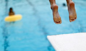 A boy jumps off a diving board into a swimming pool to cool off, in Solana Beach